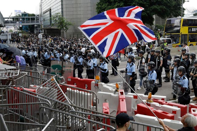 A man waves a British flag as policemen stand guard