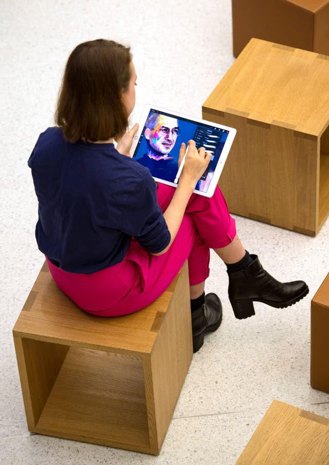 A woman uses an iPad to draw a picture of Apple founder Steve Jobs at the Apple Store on Regent Street, London,.