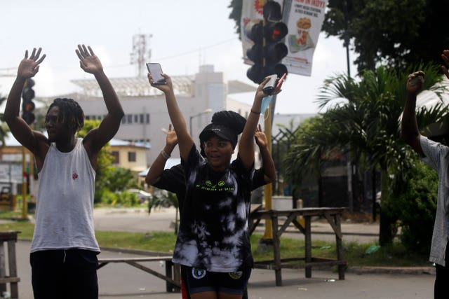 People rise their hands as they approach a police checkpoint in Lagos (Sunday Alamba/AP)