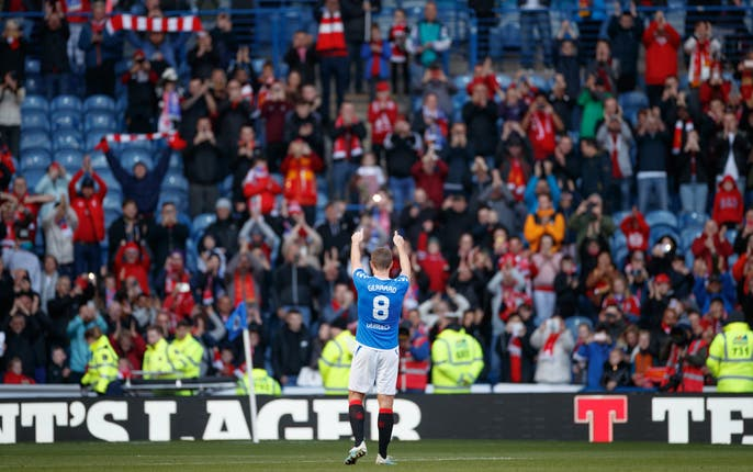 Steven Gerrard applauds the travelling supporters after playing for both teams during a Rangers v Liverpool legends match at Ibrox
