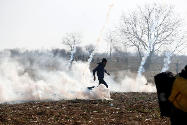 A migrant runs to avoid tear gas thrown by Greek police