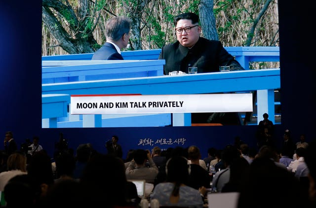 A big screen shows live video of the two leaders in private talks (Lee Jin-man/AP)