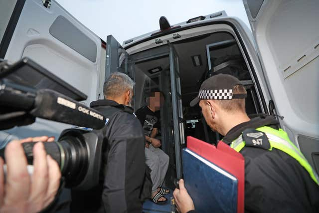 A suspect is put in the back of a police van following a raid at an address in Stockton, Teesside, as part of a crackdown on people trafficking and serious sexual offences. (Owen Humphreys/PA)