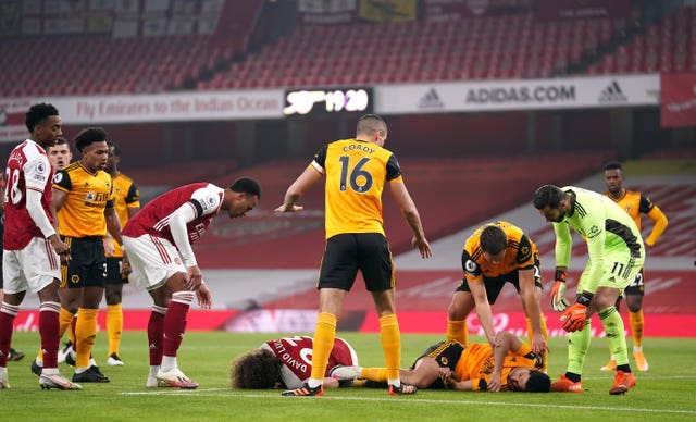 Players show concern after a serious clash of heads between Wolves' Raul Jimenez and David Luiz of Arsenal