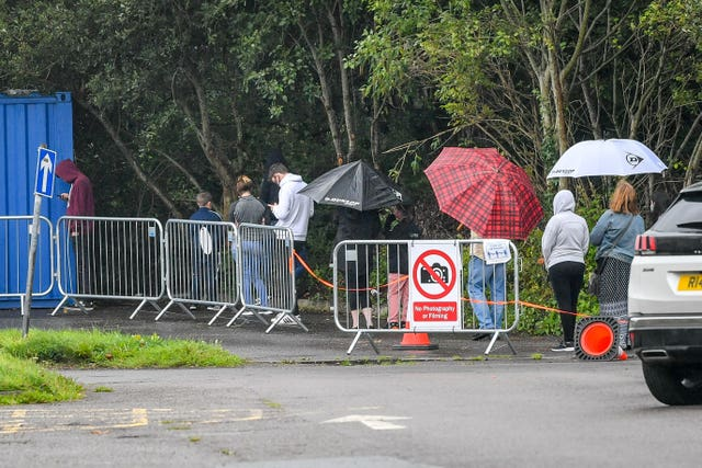 People wait in a long queue to access the walk-up coronavirus testing centre at Caerphilly Leisure Centre (Ben Birchall/PA)