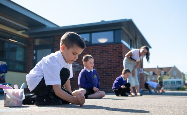 Reception pupil Ollie draws with chalk in the playground at Queen's Hill Primary School in Costessey, Norfolk