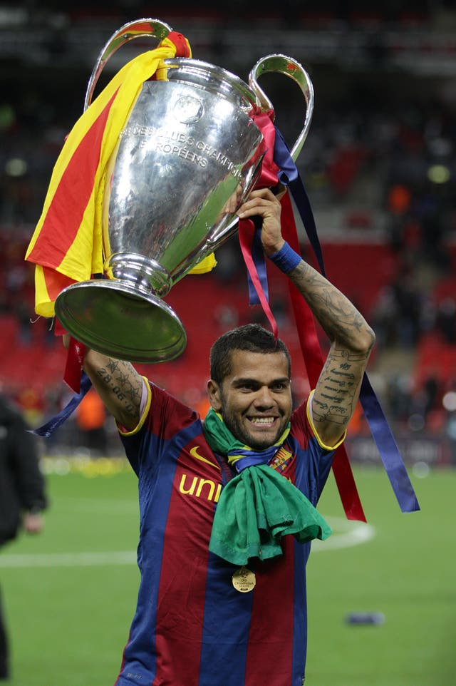 Dani Alves celebrates with Champions League trophy. (PA)