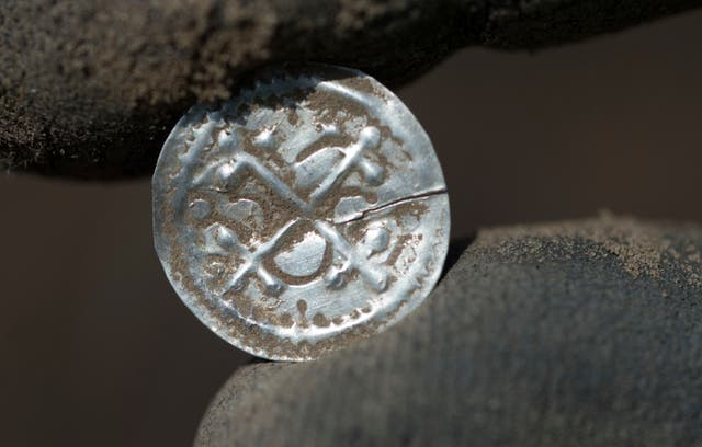 An archaeologist holds an ancient Danish coin which was minted under King Harald Bluetooth (dpa/AP)