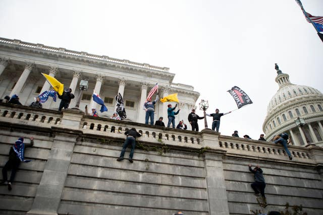 People loyal to Donald Trump climbing the west wall of the the US Capitol