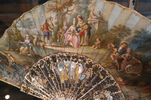 A hand fan representing a musical relaxing moment (detente musicale) is pictured at the hand fan-making museum in Paris