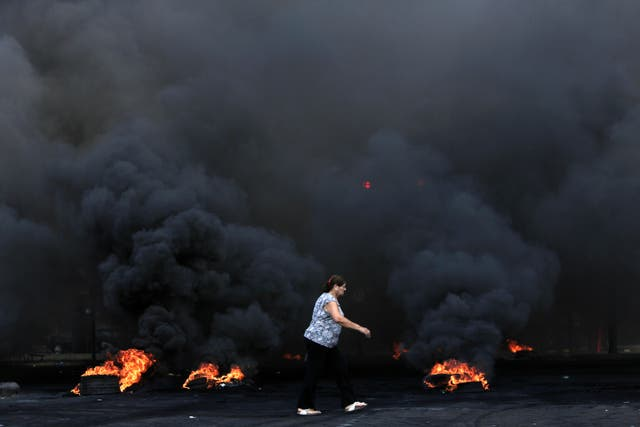 Burning tyres block a road in Beirut
