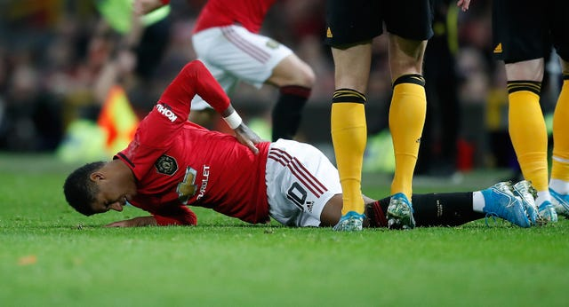 Marcus Rashford holds his back after suffering the injury against Wolves