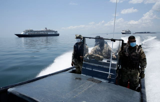 Panamanian navy police navigate near the anchored Zaandam cruise ship
