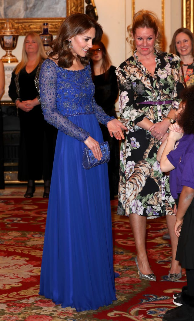 The Duchess of Cambridge speaks to members of a school choir as she hosts a gala dinner at Buckingham Palace
