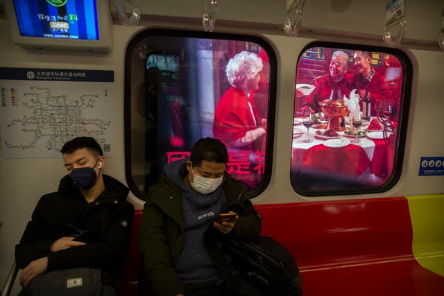 People wear masks on a subway train as it stops near a billboard showing a family having a New Year's banquet meal in Beijing