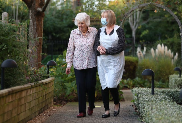 Sandy helps her mother Doreen walk around the grounds of Sunrise of Bassett care home in Southampton (Andrew Matthews/PA)