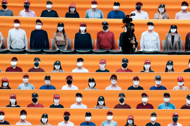 A TV cameraman walks through the spectators' seats which are covered with pictures of fans before the start of a regular season baseball game between Hanwha Eagles and SK Wyverns in Incheon, South Korea