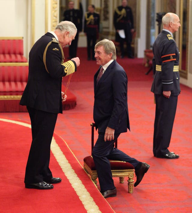 Kenny Dalglish kneels to be knighted by the Prince of Wales at Buckingham Palace.