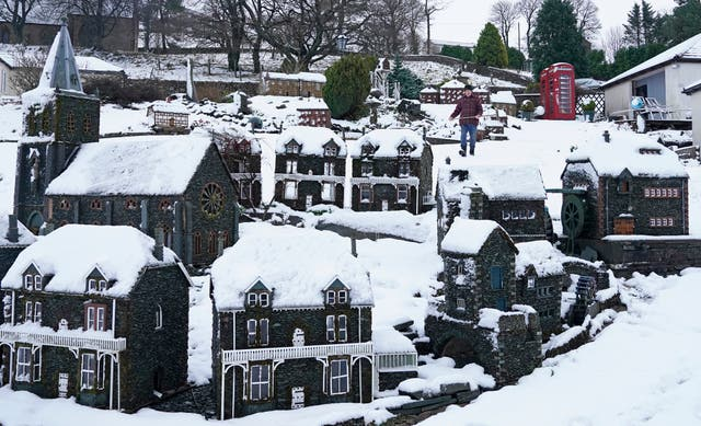 Lawson Robinson clears snow from his Nenthead miniature village in Cumbria after Storm Freya hit Britain
