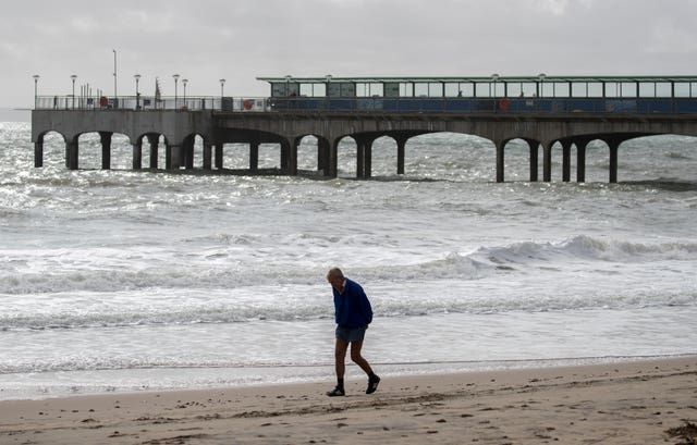 A hardy soul walks along an otherwise deserted Boscombe beach in Dorset