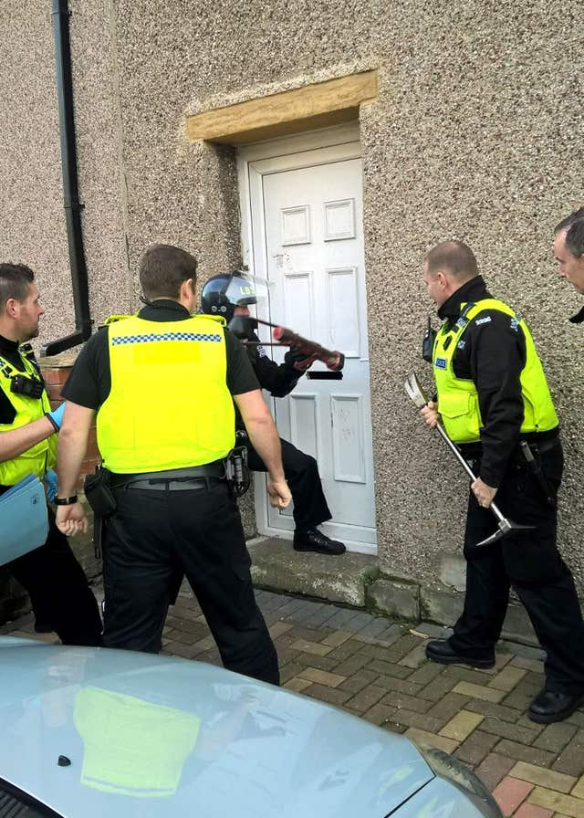 Police entering a property in Blyth, Northumberland, which belongs to Harjit Bariana (Northumbria Police/PA)