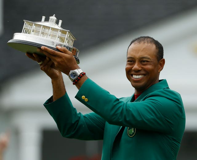 Tiger Woods wears his green jacket holding the winning trophy at the Masters