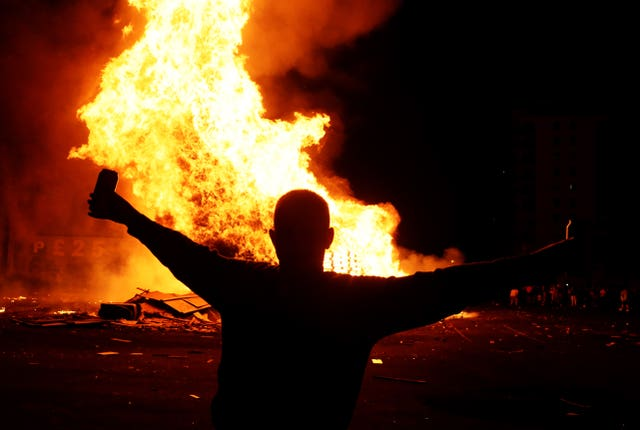 People attend a bonfire in the Sandy Row area of Belfast