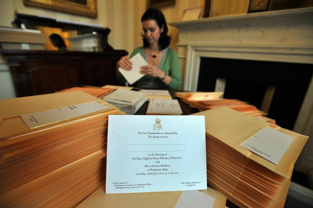 A member of the Lord Chamberlain's Office at Buckingham Palace in London, inserts the invitations into envelopes, for the wedding of Prince William and Kate Middleton (John Stillwell/PA)
