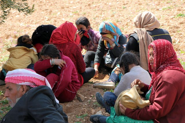Syrians fleeing fighting between Turkish troops and Syrian Kurdish militia rest in a field between Afrin and Azaz (DHA-Depo Photos via AP)
