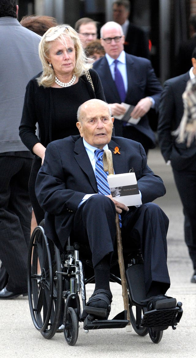 Debbie Dingell pushes the wheelchair of her husband John Dingell