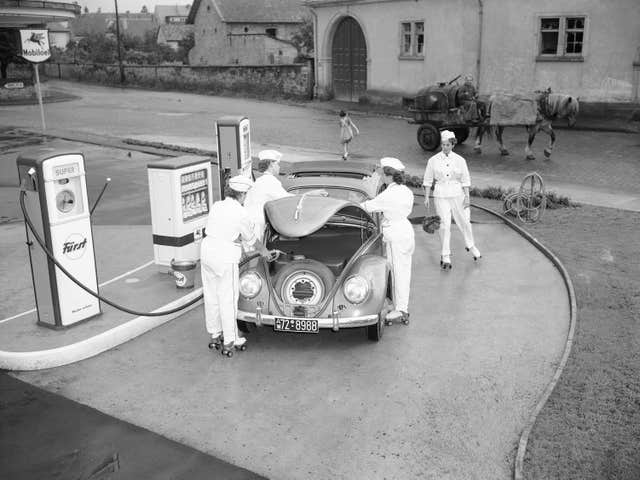 Four female employees tend to a Volkswagen at a petrol station in Deidesheim, near Kaiserslautern, Germany, in 1954
