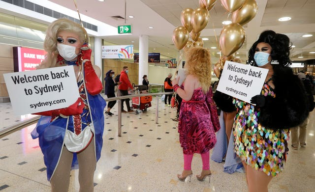 Passengers from New Zealand are welcomed by drag queens as they arrive at Sydney Airport