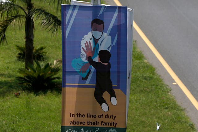 A banner paying tribute to doctors who are offering care and saving lives during the coronavirus pandemic is displayed on a road in Islamabad, Pakistan (Anjum Naveed/AP)