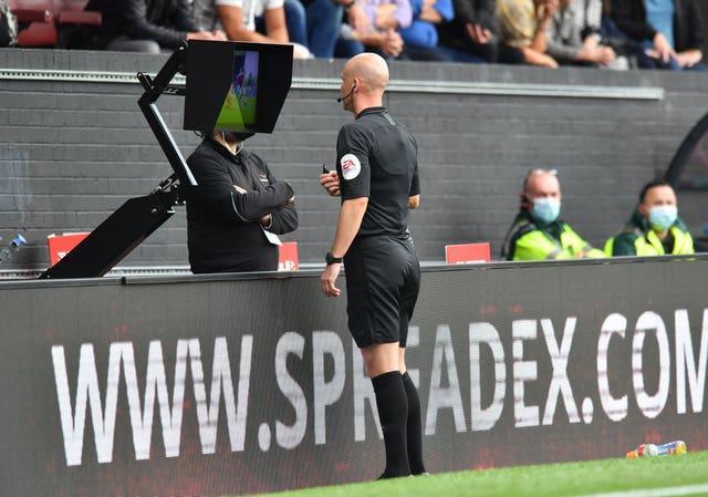 Referee Anthony Taylor checks the monitor