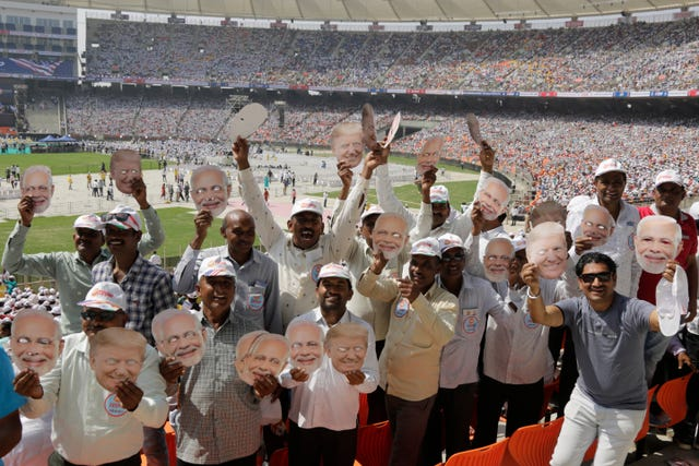 Indians hold masks of US President Donald Trump and Prime Minister Narendra Modi at Sardar Patel Stadium in Ahmedabad