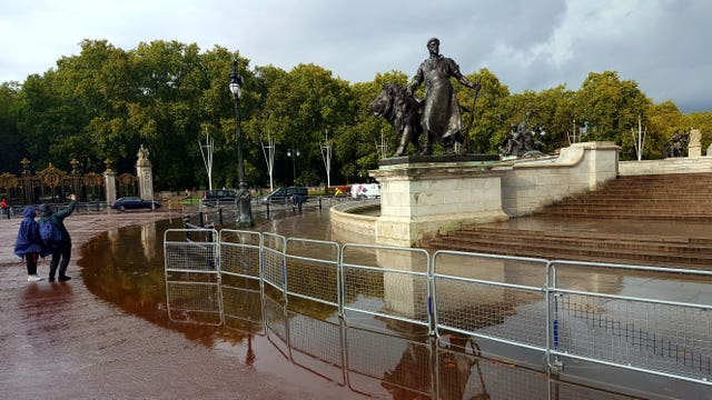 Tourists take a selfie by a flooded Queen Victoria Memorial outside Buckingham Palace