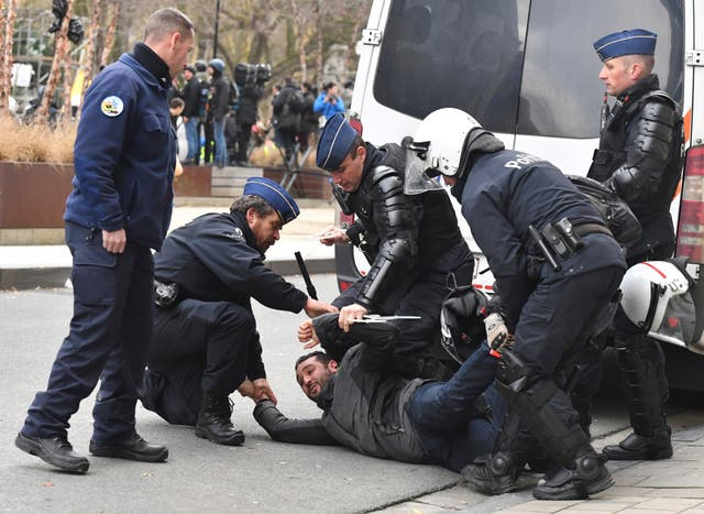 Police detain a protestor in the European Quarter in Brussels
