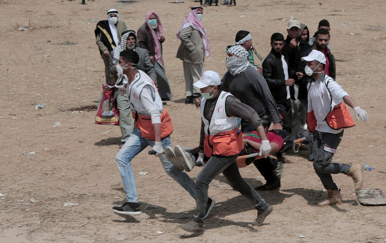 Palestinian medics and protesters carry a wounded youth