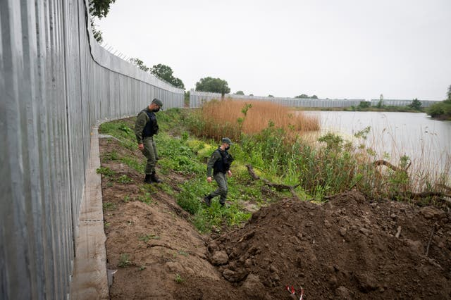 Police officers patrol along a steel wall at the Evros River, near the village of Poros, on the Greek-Turkish border, Greece