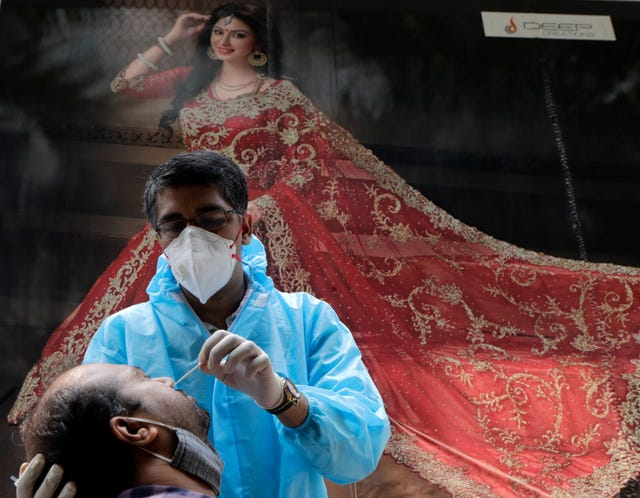 A health worker takes swab sample of a woman to test for Covid-19 outside a garment shop in Mumbai, India (Rajanish Kakade/AP)
