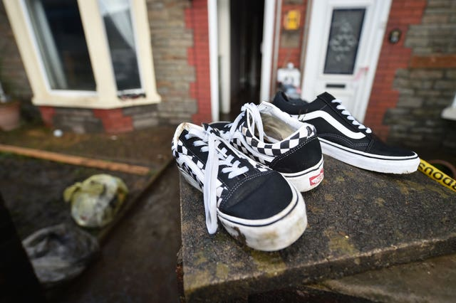 A pair of Vans trainers are left to dry out on a wall outside a property on Oxford Street, Nantgarw (Ben Birchall/PA)