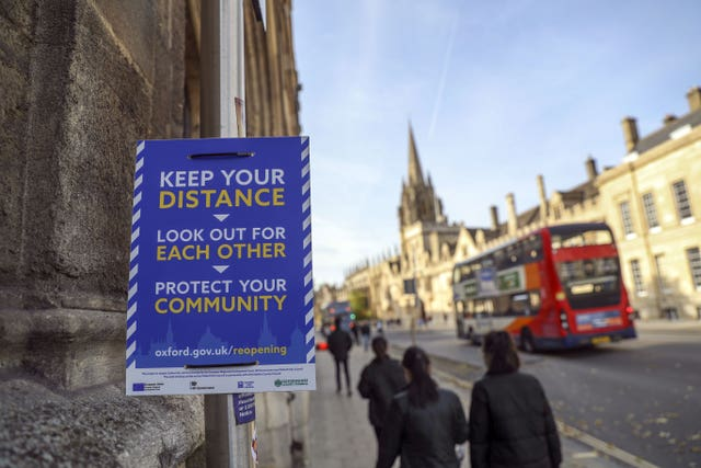Students walk past a Covid-19 sign in Oxford (Steve Parsons/PA)