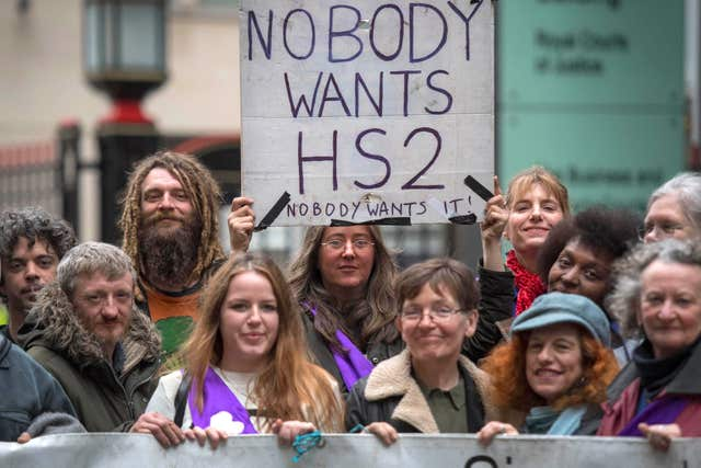 Protesters make their views known as Chris Grayling launched a High Court action to stop 'unlawful protest' by demonstrators opposed to HS2 running through a woodland area in west London (Victoria Jones/PA)