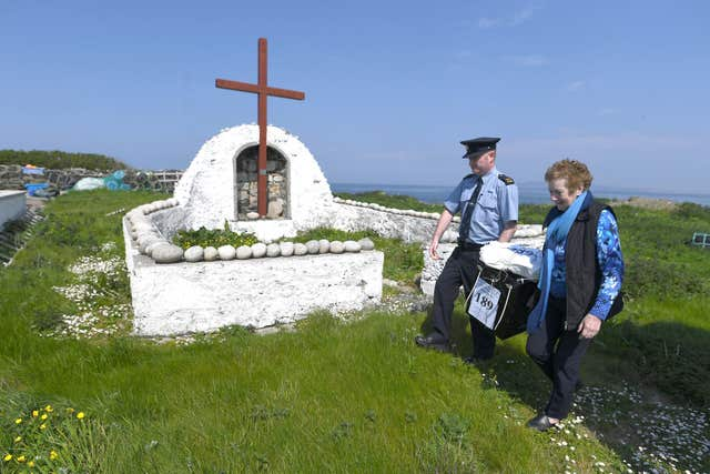Garda Alan Gallagher and Presiding Officer Carmel McBride carry a polling box, used a day early, by the few people that live off the coast of Donegal on the island of Inishbofin, to vote in the referendum (Clodagh Kilcoyne/PA)