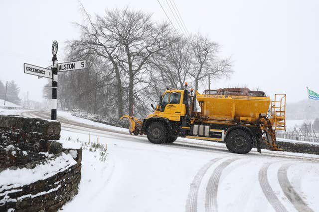A snowplough clears a road in Cumbria as the snow sets in (Owen Humphreys/PA)
