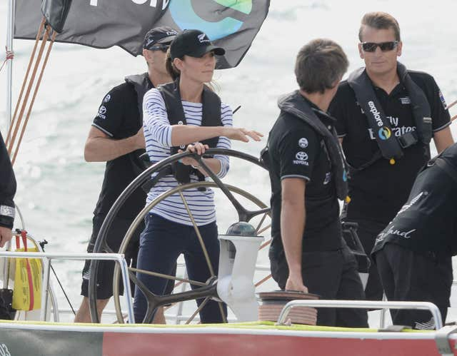 Kate steers a yacht as she competes against William in a race featuring Americas Cup yachts during their 2014 visit to New Zealand. Anthony Devlin/PA Wire