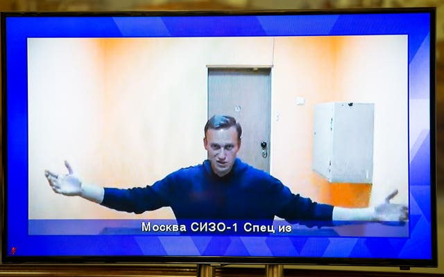 Russian opposition leader Alexei Navalny appears on a TV screen during a hearing of his appeal in a court in Moscow, Russia