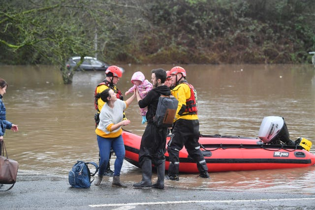 A family is taken to safety after flooding in Nantgarw