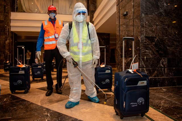 The luggage of pilgrims is sanitised in a hotel lobby in Mecca (Ministry of Media/AP)