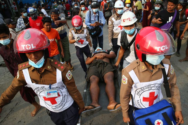 Red Cross workers carry a man on a stretcher in Mandalay, Myanmar
